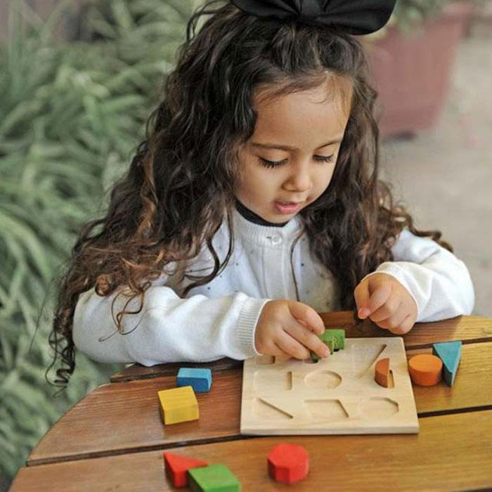 دختر در حال بازی با صفحه اشکال 9 قطعه